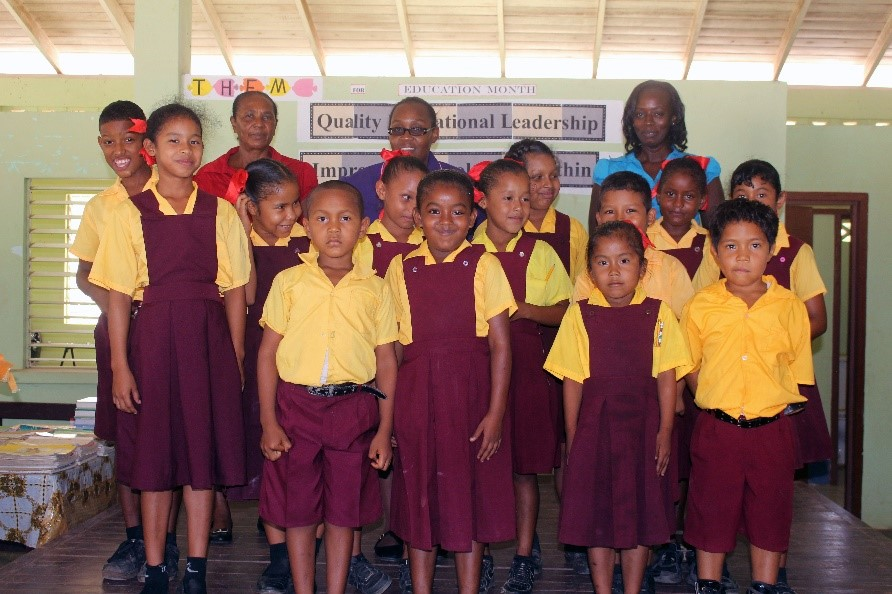 Head Teacher, Ms. Michelle Downer (extreme left) with some of her teachers and pupils.
